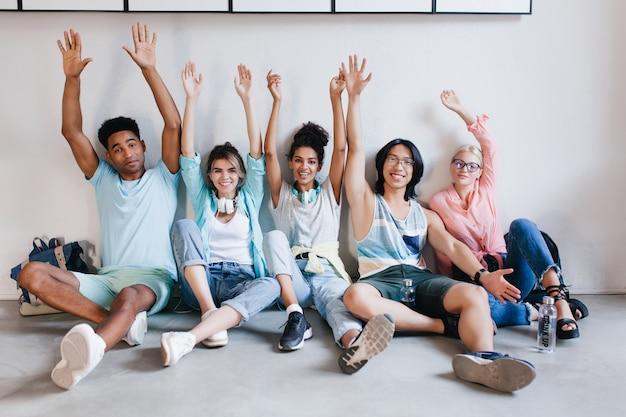 Geïnspireerde studenten poseren graag met hun handen omhoog omdat examens voorbij zijn. binnenportret van zalige universiteitsgenoten die voor de vakantie plezier hebben op de campus.