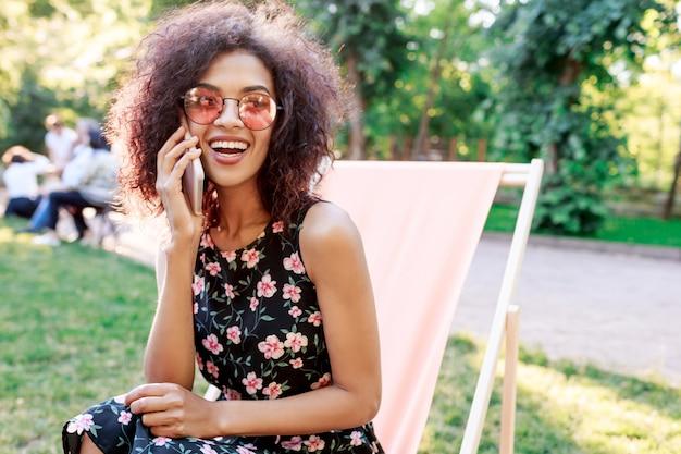 Geïnspireerde vrouw die met krullende haren in de zomerpark ontspannen in zonnig weekend. genieten van vrije tijd in de natuur. mobiele telefoon praten en lachen.