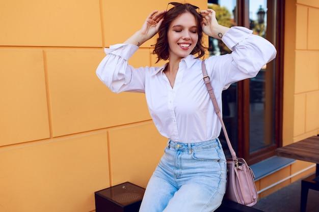 Geïnspireerde vrouw met overhemdsharen die van weekends in zonnige europese stad genieten. casual blouse dragen.