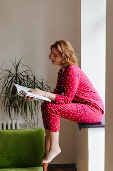Geïnspireerde vrouw zittend op de vensterbank en tijdschrift lezen. binnen schot van blote voeten vrouw in pyjama.