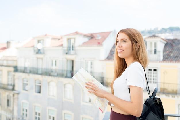 Geïnspireerde vrouwelijke toerist die van schoonheid van stad geniet