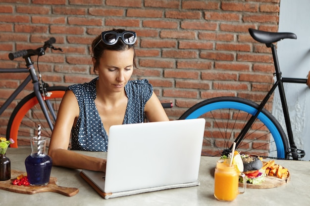Geïnspireerde vrouwenblogger die aan een nieuwe post voor haar blog werkt, opmerkingen van haar volgers leest en glimlacht. vrouw met tinten op haar hoofd genieten van online communicatie