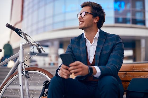 Geïnspireerde zakenman die op bank met smartphone in stad rust