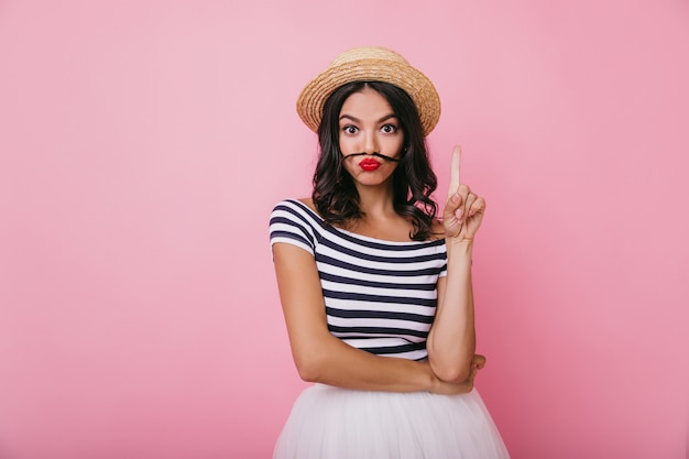 Geïnteresseerd brunette meisje met rode lippen gek rond. portret van blithesome blanke vrouw poseren in stijlvolle strooien hoed.