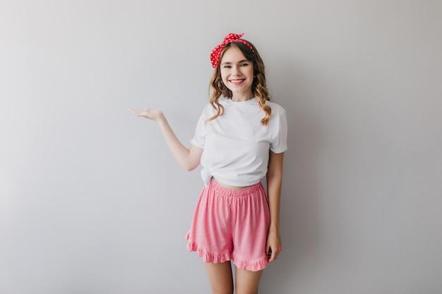 Geïnteresseerd europees meisje in nachtkleding met plezier. verfijnde witte dame in roze korte broek poseren met charmante glimlach.