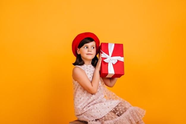 Geïnteresseerd kind raadt wat er in de huidige doos zit. preteen feestvarken geïsoleerd op gele muur.