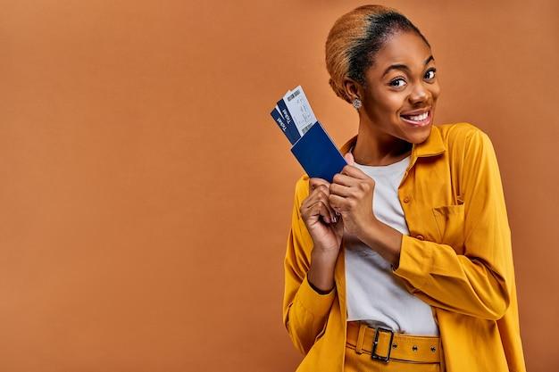 Geïnteresseerd meisje in een geel pak heeft een paspoort met kaartjes met twee handen. reis concept