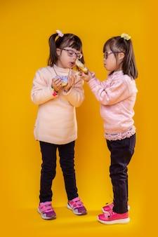 Geïnteresseerd om eraan te snuiven. schattige kleine meisjes met chromosoomafwijkingen die spelen met voorgesteld voedsel