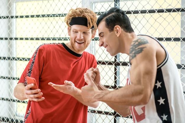Geïnteresseerd. twee basketballers kijken naar iets op de smartphone en kijken erbij betrokken