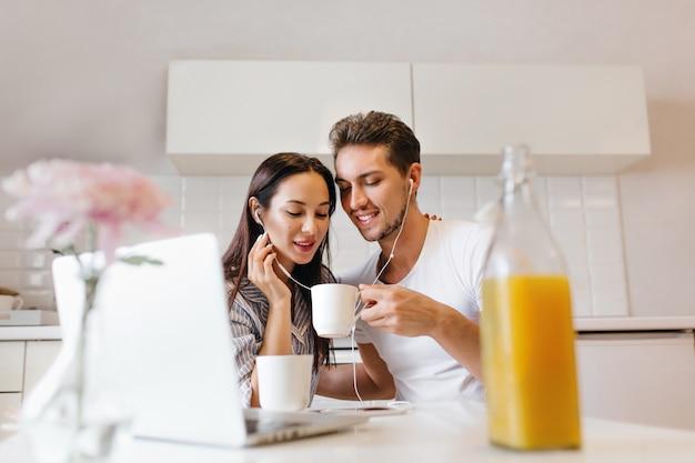 Geïnteresseerd vrouwelijk model in witte oortelefoons lachen met echtgenoot tijdens gezamenlijke lunch