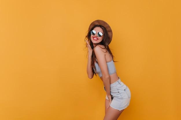 Geïnteresseerd, welgevormd meisje in zonnebril die voor de gek houdt tijdens indoor fotoshoot