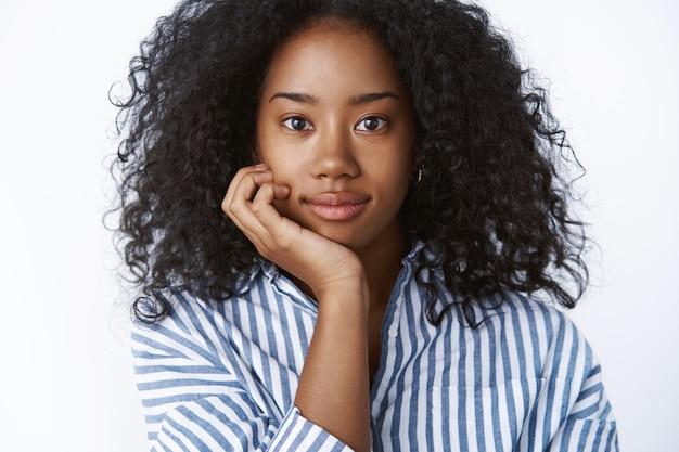 Geïnteresseerde aantrekkelijke jonge afro-amerikaanse vrouwelijke universiteitsstudent met krullend haar woont een interessante lezing bij, leunend hoofdpalm kijkt geïntrigeerd nieuwsgierig luistert tevreden glimlacht, ziet er gelukkig uit