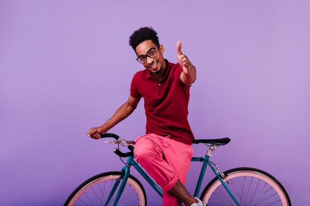 Geïnteresseerde afrikaanse mannelijk model poseren. stijlvolle zwarte jongen die in glazen op blauwe fiets zit.
