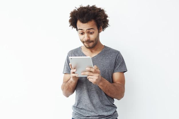 Geïnteresseerde afrikaanse mens die tablet over witte bakground bekijken.