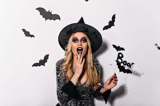 Geïnteresseerde blonde vrouw in heksenkostuum die speels op witte muur stellen. vrouwelijke vampier omringd door vleermuizen.