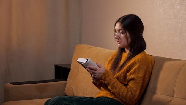 Geïnteresseerde dame met lang los haar houdt papieren boek in handen en leest zittend op een comfortabele bank met bruine kussens slow motion close-up