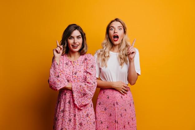 Geïnteresseerde dames in trendy kleding die zich voordeed op een lichte muur. portret van nieuwsgierige vriendinnen die zich voor gele muur bevinden.