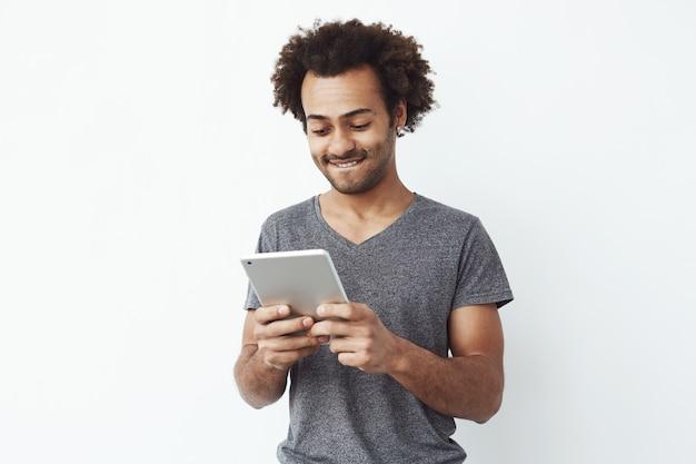 Geïnteresseerde en geconcentreerde jonge afrikaanse mens die tablet bekijkt die een platformgamespel speelt en van nieuwe niveaus over witte bakground geniet.