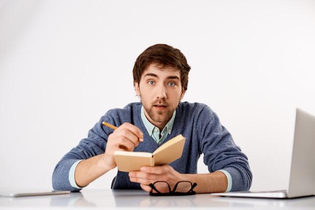 Geïnteresseerde jonge bebaarde man, leer nieuwe taal online cursussen terwijl je thuis in quarantaine zit, noteer in een notitieboekje en kijk geïnteresseerd
