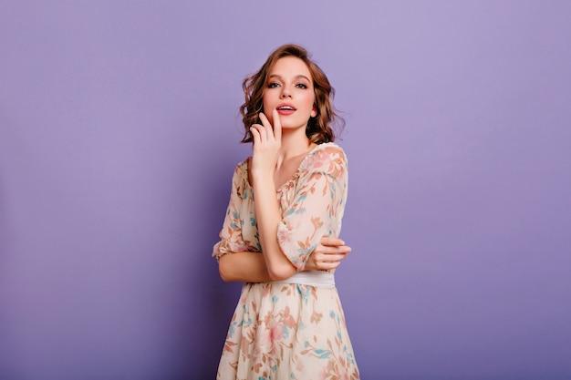 Geïnteresseerde jonge dame in lichte jurk met bloemmotief op zoek naar camera