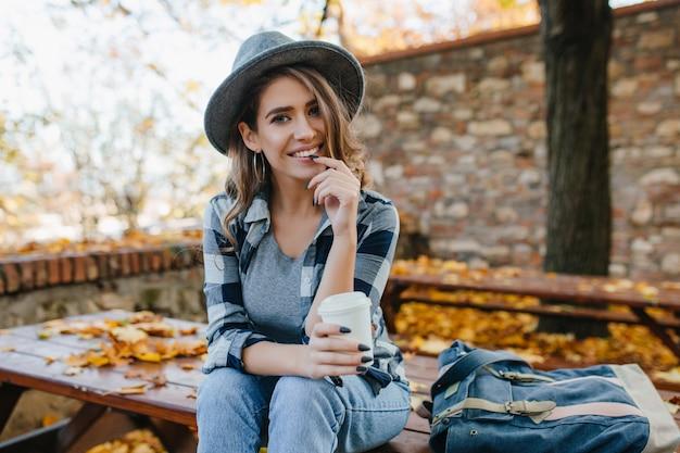 Geïnteresseerde jonge dame met kopje koffie poseren in park in oktober dag