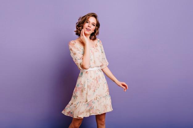 Geïnteresseerde jonge vrouw in schattige jurk zachtjes aanraken van haar gezicht op paarse achtergrond