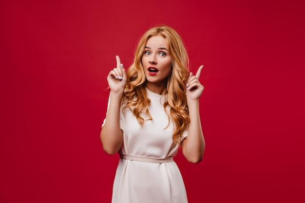 Geïnteresseerde jonge vrouw met lang golvend haar poseren met open mond. debonair stijlvol meisje in witte jurk staande op rode muur.