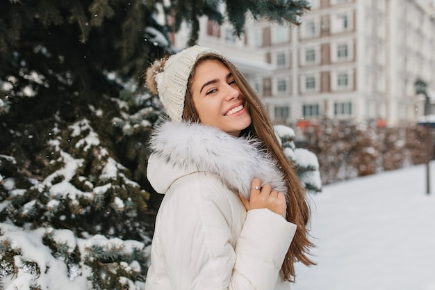 Geïnteresseerde langharige vrouw in witte kledij genieten van gelukkige wintertijd en lachen. openluchtportret van prachtige europese vrouw in gebreide muts die zich bij besneeuwde straat bevindt