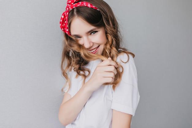 Geïnteresseerde mooi meisje poseren met een verlegen glimlach. indoor foto van emotionele krullende vrouw draagt rood lint.