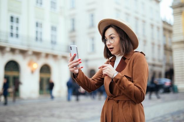 Geïnteresseerde mooie jonge vrouw lopen op straat in warme dag