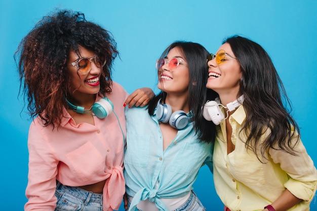 Geïnteresseerde mulat vrouwelijk model kijkend met glimlach naar aziatische meisjes draagt grote koptelefoon. trendy dames in kleurrijke kleding praten rond.