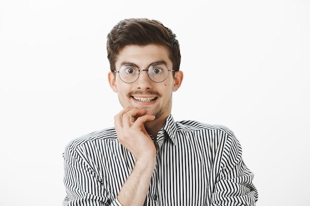 Geïnteresseerde nerdy officemanager die met verleiding door een bril naar een nieuwe computer in de winkel kijkt, zenuwachtig lacht, een nieuwe gadget wil kopen, ongeduldig en blij over de grijze muur staat