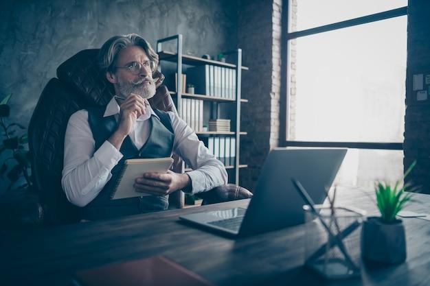 Geïnteresseerde oude zakenman houdt voorbeeldenboek denken op kantoor
