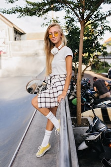Geïnteresseerde slanke vrouw met lang blond haar poseren op straat met skateboard.