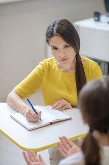 Geïnteresseerde slimme mooie vrouw in gele blouse zittend aan tafel met pen en meisje vooraan