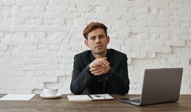 Geïnteresseerde stijlvolle ontwerper luistert naar de klant en wrijft in zijn handen