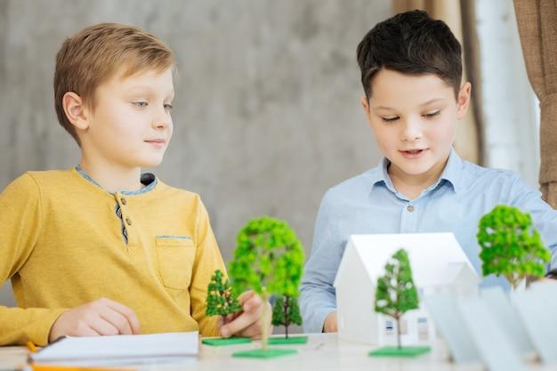 Geïnteresseerde studenten. charmante pre-tienerjongens die het project van ecostad onderzoeken, miniatuurmodellen onder de loep nemen en ze bespreken terwijl ze de werkplek van hun vader bezoeken
