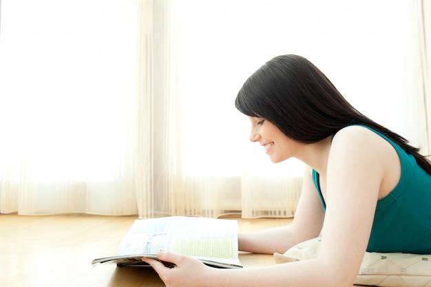Geinteresseerde vrouw die een tijdschrift leest dat op de vloer ligt