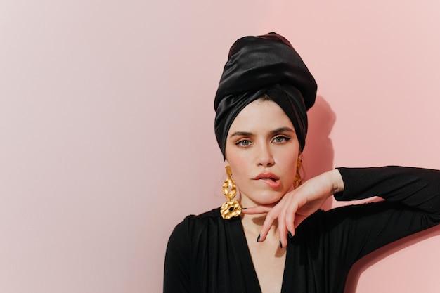 Geïnteresseerde vrouw in tulband staande op lichte muur