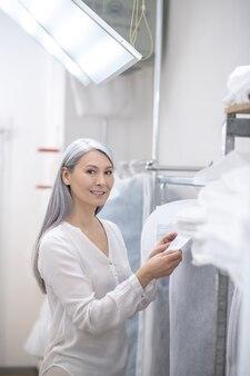 Geïnteresseerde vrouw met lang grijs haar staande in verlichte kamer in de buurt van kledingrek label kijken