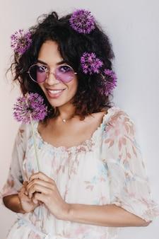 Geïnteresseerde zwarte vrouw met stijlvol kapsel poseren met paarse bloem. prachtig afrikaans vrouwelijk model dat allium vasthoudt en kijkt.