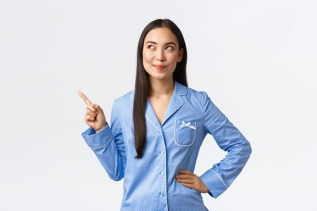Geïntrigeerd aziatisch meisje in blauwe pyjama's kijken en wijzende vinger in de linkerbovenhoek naar iets