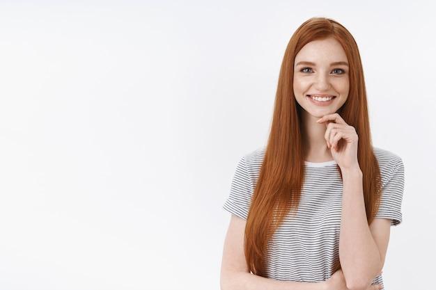 Geïntrigeerd enthousiast creatief jong schattig meisje freelancer op zoek onder de indruk tevreden glimlachend opgetogen aanraking kin denken interessant idee bekijk geweldig project, staande witte muur
