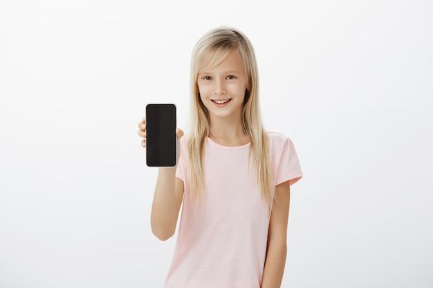 Geïntrigeerd keurig blond meisje in roze t-shirt, nieuwsgierig glimlachend en met zwarte smartphone