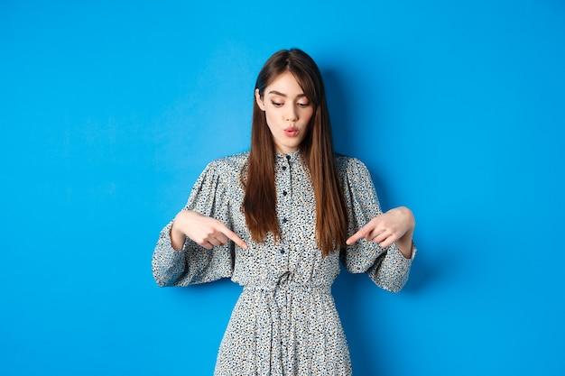 Geïntrigeerd mooi meisje in jurk zegt wow, kijkend en wijzend naar advertentie, toont promo met geïnteresseerd gezicht, blauw.