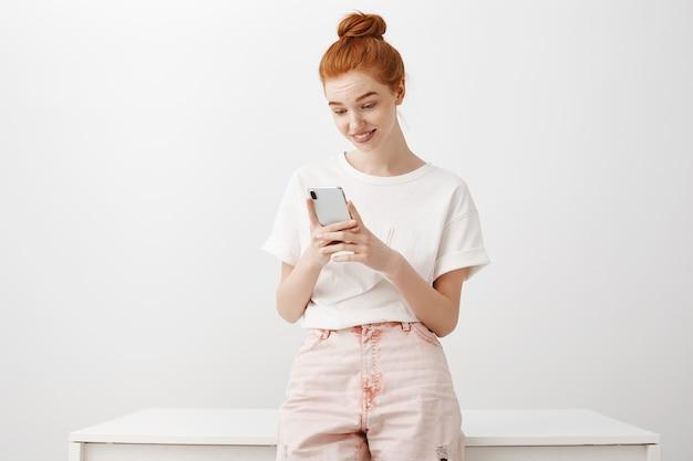 Geïntrigeerd roodharig meisje dat geïnteresseerd is in mobiele telefoon