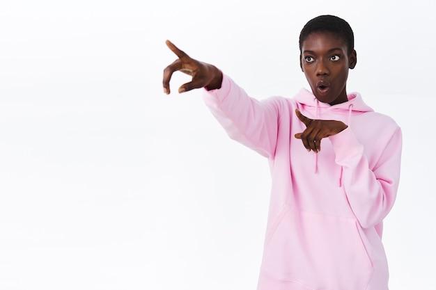 Geïntrigeerde en nieuwsgierige jonge afro-amerikaanse stijlvolle vrouw in roze hoodie