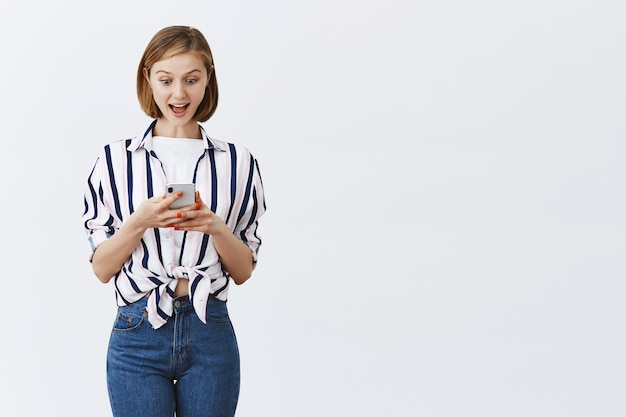 Geïntrigeerde en opgewonden jonge vrouw die berichten of bankrekening op telefoon controleert, verbaasd kijkend naar smartphone