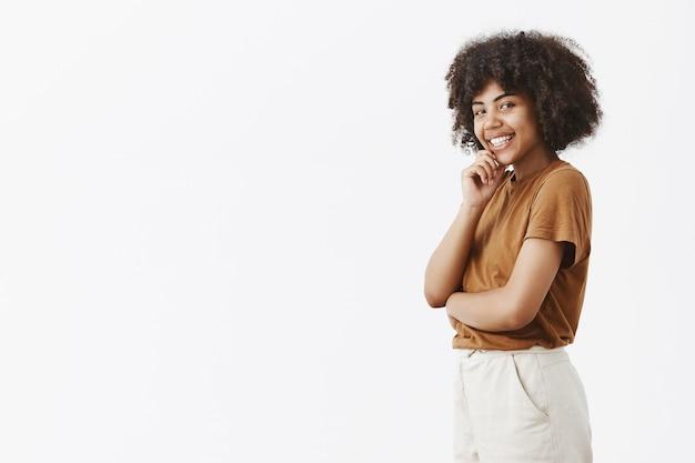 Geïntrigeerde flirterige vrouwelijke donkere vrouw met afro kapsel in bruin t-shirt permanent in profiel, draaien met schattige glimlach hand op kin vasthoudend met interesse en verlangen