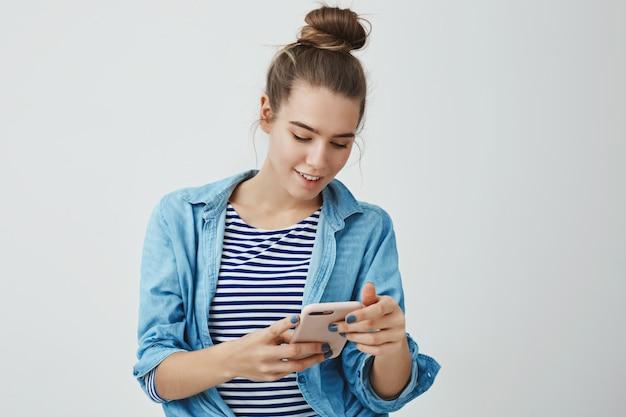 Geïntrigeerde geamuseerde knappe modieuze vrouw 25s die interessant uitnodigingsbericht leest dat smartphone houdt kijkend vertoning opgewekt glimlachend breed